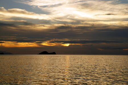 Landscape of natural sandy beaches of coast Southern - the Chinese sea of peninsula Seantubong to Borneo. Sunset. photo