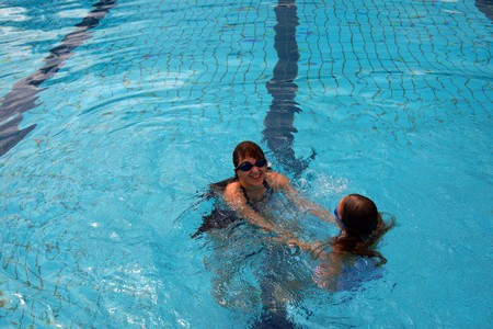 Young beautiful mum together with the beauty a daughter study to float in a swimming pool. photo