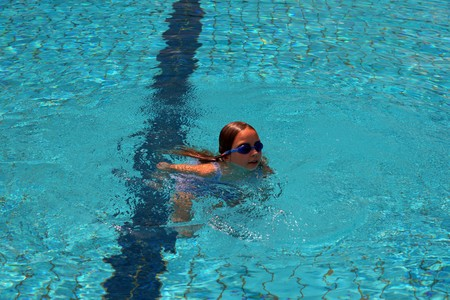 The beautiful girl the child studies to swimm in a swimming pool. photo