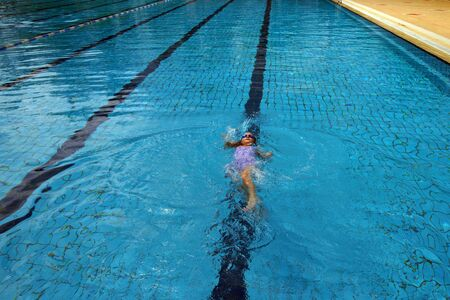 swimm: The beautiful girl the child studies to swimm in a swimming pool. Stock Photo