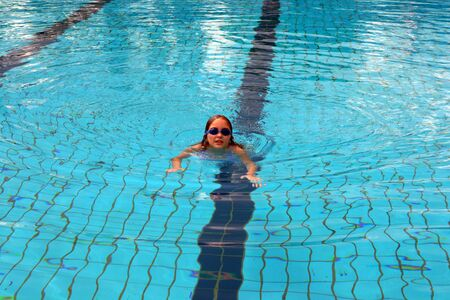 The beautiful girl the child studies to swimm in a swimming pool. Stock Photo