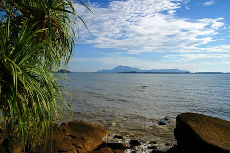 The blue sea of the stony coast which have grown with jungle of peninsula Santubong. Borneo. Stock Photo