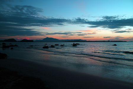 Sea sunset at stony sea coast of peninsula Santubong. Borneo.