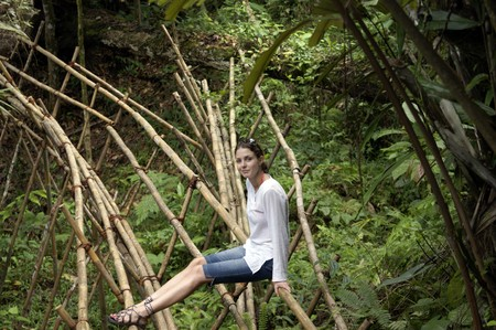 The beautiful young girl cautiously goes on the bamboo bridge in mountains Borneos near to border with Kalimantan Stock Photo