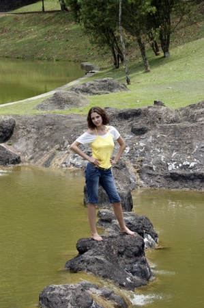 The young beautiful girl on a stony crossing through tropical lake to Borneo. photo