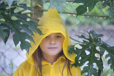 The beautiful girl the teenager plays about under a tropical rain on a back court yard of the house to Borneo. photo
