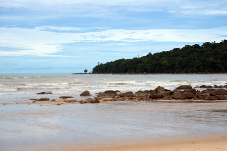 The dark blue sea of the stony coast which have grown with jungle of peninsula Santubong. Borneo.  Stock Photo