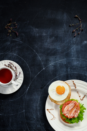 bacon baked beans: Tea with thyme and breakfast of bacon and eggs on a blackboard. View from above Stock Photo
