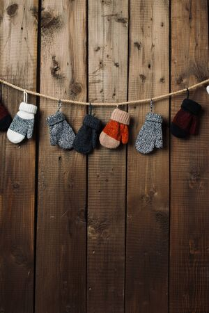 Vintage brown old wood texture wall background with garland of childrens mittens on rope