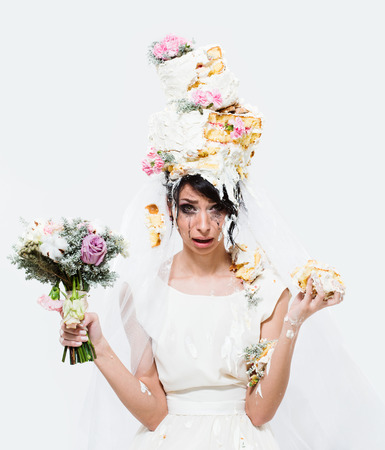 Beautiful unhappy crying brunette bride with cake on her head on white background. Front view. Stock Photo