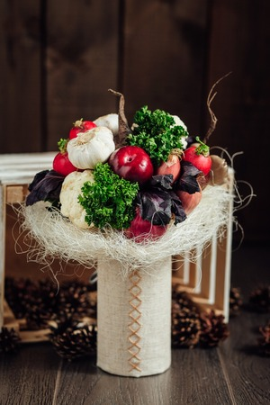 unusual vegetables: The original unusual edible bouquet of vegetables and fruits on a dark wood with cones around it