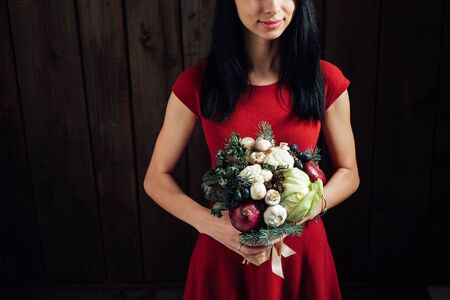 red hand: The original unusual edible bouquet of vegetables and fruits in the girl hands on dark wooden background