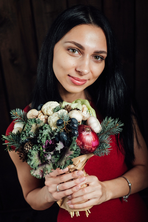 unusual vegetables: The original unusual edible bouquet of vegetables and fruits in the girl hands on dark wooden background