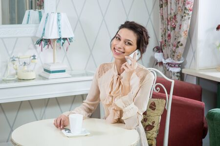 tea lamp: beautiful brunette girl sitting at a table in the French Provence style cafe and lamp on background with a cup of tea or coffee, indoor shot. Stock Photo