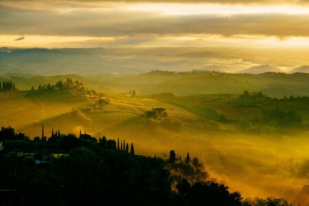 Dawn in a misty valley in the hills in Tuscany, Italy