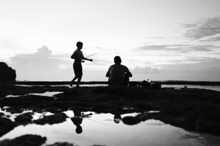 Silhouettes of two people fishing on the island of Bali, Indonesia - black and white photo