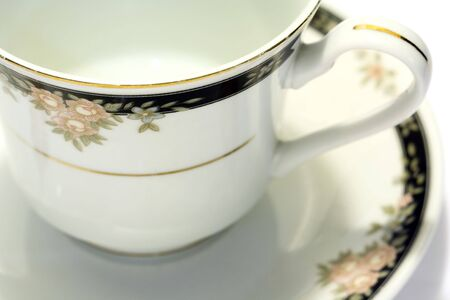 Close-up of porcelain tea cup and saucer with white background
