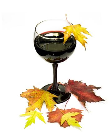 Glass of red vine with multicolor fall leafs