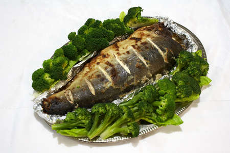 Baked pink salmon served with broccoli on a white tablecloth
