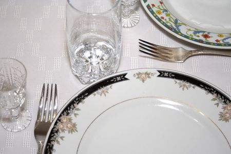 Close-up of served table with wineglass and plates
