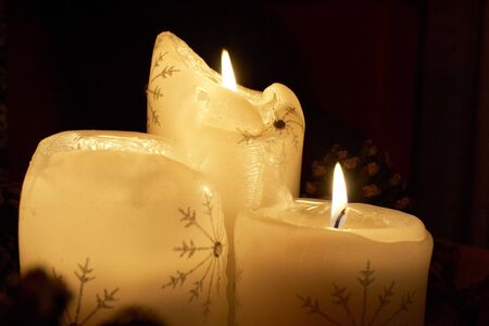 cutting through: A trio of Xmas candles cutting through the darkness Stock Photo