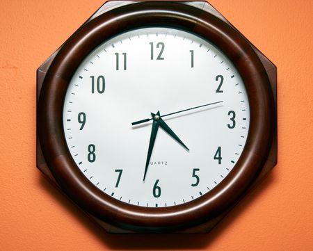 Modern clock on orange wall photo