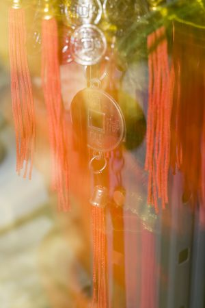 Motion close-up of Chinese Symbolic spiritual pendant with vintage coins, red lace and tassel