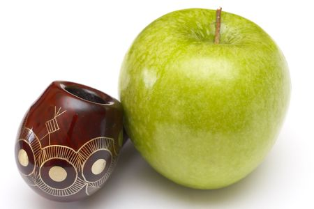 Long ornamented north-caucasian pipe with big green apple at white background