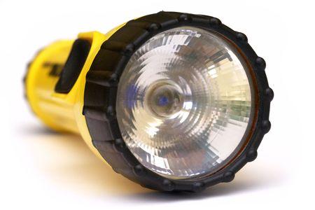 Yellow and black flashlight with white background photo