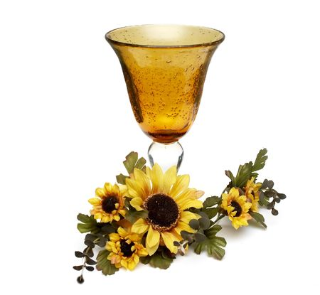 Big yellow wineglass with bouquet of artificial sunflower isolated with white background