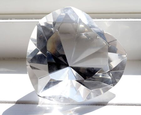 Macro close-up of giant crystal heart under sunsine at the window-sill Stock Photo