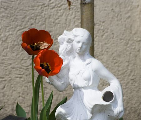 Statue of girl with pitcher near red tulips