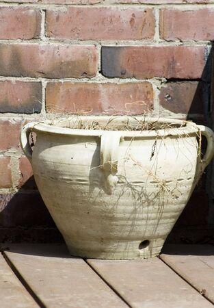 Old pot near briked wall Stock Photo