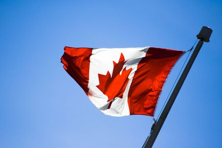 Canadian flag in a blue sky Stock Photo