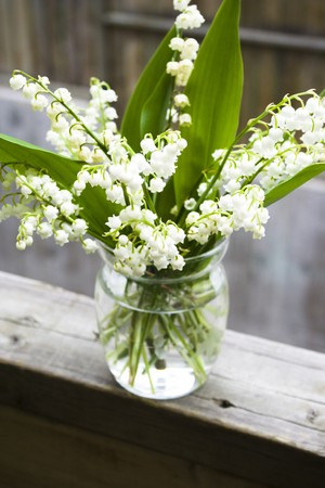 lily of the valley: bouquet of lily of the valley in glass vase at the wood handrail