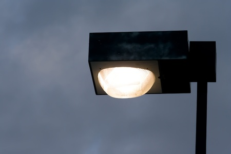 Close up of black boxed street light lighting in the night sky