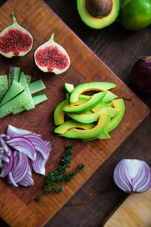 figs, avocado, cucumber, arugula, red onion, thyme on a cutting wooden board close-up - salad ingredients Banco de Imagens - 133083700