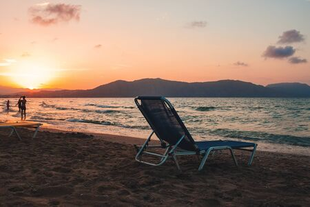empty beach chair on a sandy beach on a sunset background. The sun sets in the mountains on Crete, Greece Banco de Imagens