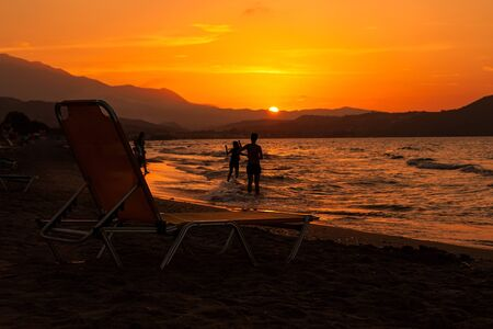 Sunbed on the beach at sunset. Crete Banco de Imagens