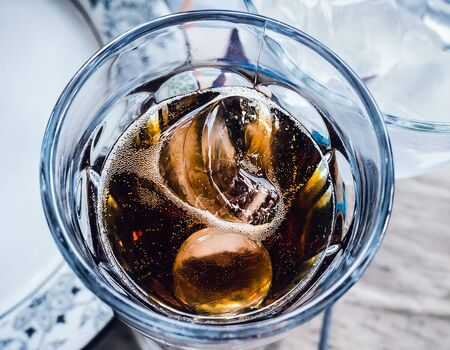 two pieces of ice float in a glass with a dark carbonated drink. Close-up Фото со стока