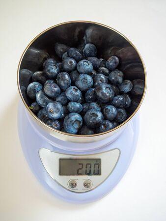 200 grammi di mirtilli puri maturi in una ciotola di metallo con bilancia elettronica bianca