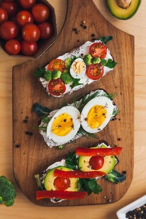 three bruschettas on dark bread with curd cheese, eggs, vegetables, spices and herbs on a wooden board