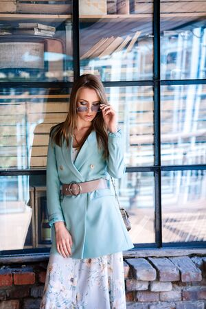attractive model with brown hair in a blue jacket, skirt, sunglasses looks down. Shot outdoors against a loft window