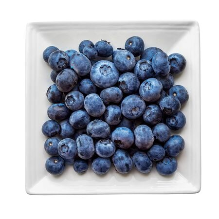 a lot of ripe blueberries on a square plate on a white background. Isolated without shadow.