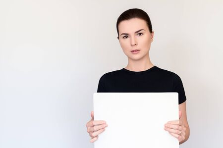 beautiful woman with dark hair and brown eyes in a black T-shirt on a white background holds a tablet without text. Copy space for text. Portrait medium plan Archivio Fotografico