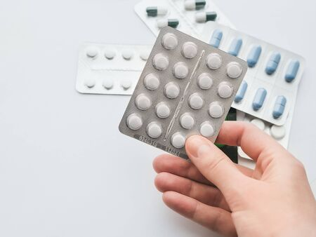 20 white tablets in a silver blister in hand close-up. The concept of drug treatment. Copy space for your text on a white background. Standard-Bild