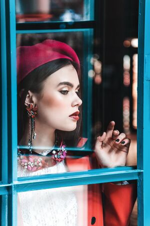very beautiful brunette model with blue eyes in a red beret is looking through the glass. Skin retouching.