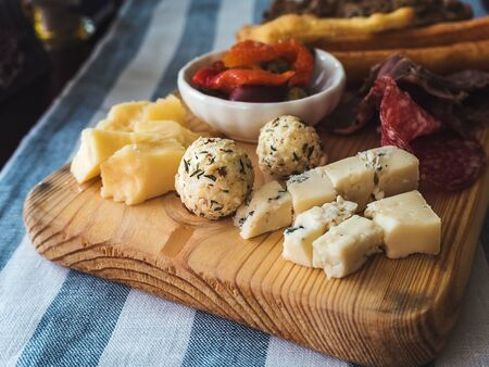 Assorted cheeses and sausages on a wooden board on a table with a linen striped tablecloth