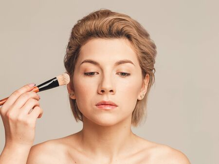 applying foundation on a woman's face. Makeup artist training concept. Without retouching