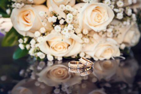 wedding rings and bouquet on black glass Standard-Bild